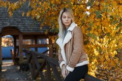 Fashionable attractive young blonde girl in a stylish autumn beige jacket and black trousers sitting on the bridge. On the background of a tree. Autumn, a woman stock images