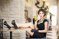 Fashionable attractive young woman in black dress sitting comfortable in restaurant. Brunette relaxing with legs on table Royalty Free Stock Photography