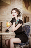 Fashionable attractive young woman in black dress sitting in restaurant. Beautiful brunette posing in elegant vintage scenery Royalty Free Stock Image