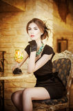 Fashionable attractive young woman in black dress sitting in restaurant. Beautiful brunette posing in elegant vintage scenery Royalty Free Stock Photography