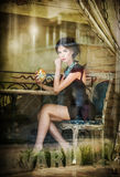 Fashionable attractive young woman in black dress sitting in restaurant, beyond the window. Beautiful brunette posing in window. Fashionable attractive young Stock Photo