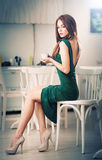 Fashionable attractive young woman in green dress sitting in restaurant. Beautiful redhead in elegant scenery with a cup of coffee. Fashionable attractive young royalty free stock images