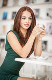 Fashionable attractive young woman in green dress sitting in restaurant. Beautiful redhead posing in elegant scenery with a coffee Stock Images