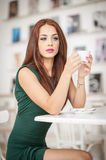 Fashionable attractive young woman in green dress sitting in restaurant. Beautiful redhead posing in elegant scenery with a coffee Royalty Free Stock Image