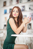 Fashionable attractive young woman in green dress sitting in restaurant. Beautiful redhead posing in elegant scenery with a coffee Royalty Free Stock Photography