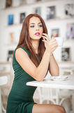 Fashionable attractive young woman in green dress sitting in restaurant. Beautiful redhead posing in elegant scenery with a coffee Stock Image