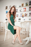 Fashionable attractive young woman in green dress sitting in restaurant. Beautiful redhead posing in elegant scenery with juice Stock Photos