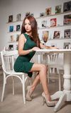Fashionable attractive young woman in green dress sitting in restaurant. Beautiful redhead posing in elegant scenery with juice Royalty Free Stock Photo