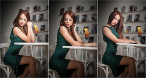 Fashionable attractive young woman in green dress sitting in restaurant. Beautiful redhead posing in elegant scenery with juice Royalty Free Stock Image