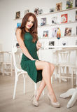 Fashionable attractive young woman in green dress sitting in restaurant. Beautiful redhead posing in elegant scenery with juice Royalty Free Stock Images