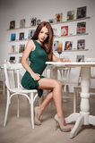 Fashionable attractive young woman in green dress sitting in restaurant. Beautiful redhead posing in elegant scenery with juice Stock Photo