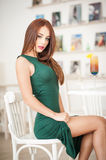 Fashionable attractive young woman in green dress sitting in restaurant Royalty Free Stock Image