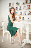 Fashionable attractive young woman in green dress sitting in restaurant. Beautiful redhead posing in elegant scenery with an orange juice glass on the table stock image