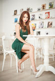 Fashionable attractive young woman in green dress sitting in restaurant Stock Photography