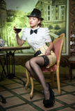 Fashionable attractive young woman with male outfit, bow and black stockings sitting in restaurant. Beautiful lady posing. In elegant vintage scenery with a royalty free stock image