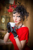 Fashionable attractive young woman in red dress drinking coffee in restaurant. Beautiful brunette in elegant vintage scenery Royalty Free Stock Photo