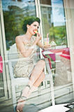 Fashionable attractive young woman tasting a lemon slice in restaurant, beyond the windows. Beautiful brunette posing Stock Photo