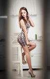 Fashionable attractive young woman in tight short dress sitting on high bar chair. Beautiful redhead on high heels posing on stool