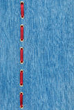 Fashionable background, red satin ribbon inserted in denim Stock Photography