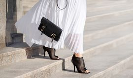 Fashionable bag close-up in female hands.Girl walks in the city outdoors. Stylish modern and feminine image, style.