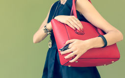 Fashionable beautiful big red handbag on a shoulder of the girl in a black dress trendy. Warm colors Stock Images