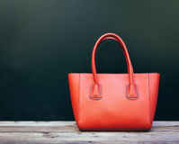 Fashionable beautiful big red handbag standing on a wooden floor on black wall background. Still life. Warm color Stock Photography