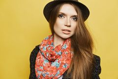 Fashionable and beautiful blonde model girl with gentle makeup in the stylish coat with leopard print, in trendy hat and. In the colorful scarf posing at the royalty free stock photography