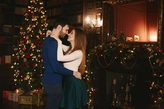 Fashionable and beautiful couple, brunette model girl with bright makeup in a skirt and stylish handsome bearded. Men hugs and posing near the Christmas tree at royalty free stock photo