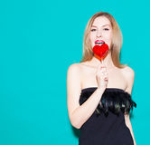 Fashionable beautiful girl biting a red lollipop and look at his. In a black dress on a green background in the studio. Look at th Royalty Free Stock Photo