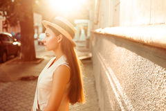 Fashionable and beautiful girl in a hat walks through sunny city. Fashionable and beautiful girl walks on the sunny city Royalty Free Stock Image