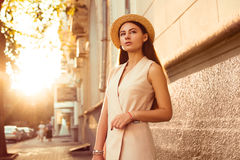 Fashionable and beautiful girl in a hat walks through sunny city. Fashionable and beautiful girl walks on the sunny city Stock Image