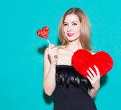 Fashionable beautiful girl holding a red candy heart and big toy heart. In a black dress on a green background in the studio. Look Stock Image