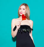 Fashionable beautiful girl holding a red candy heart. In a black dress on a green background in the studio. Fashion Beauty Girl. S Royalty Free Stock Image