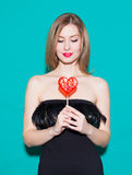 Fashionable beautiful girl holding a red candy heart and look at his. In a black dress on a green background in the studio. Fashio Royalty Free Stock Photography