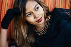 Fashionable beautiful girl posing on stripe sofa. Fashionable beautiful girl in black dress Stock Photo