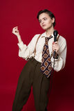Fashionable beautiful singer girl in retro coat, tie and pants with microphone in hands posing on red background. Stock Images