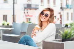 Fashionable beautiful smiling woman in round sunglasses and ice. Cream relaxing in a summer cafe stock images