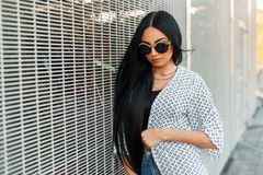 Fashionable beautiful woman with round sunglasses. In a white cloak near the wall of the grid royalty free stock photo