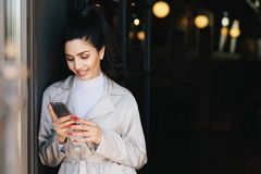 Free Fashionable Beautiful Woman With Dark Hair Tied In Pony Tail Dressed In White Elegant Coat Holding Cell Phone Looking Into Screen Royalty Free Stock Image - 125168846