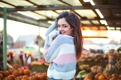 Fashionable beautiful young girl at the autumn pumpkin patch background. Having fun and posing. Toned in retro style royalty free stock images