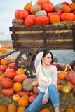 Fashionable beautiful young girl at the autumn pumpkin patch background. Having fun and posing. Toned in retro style stock photos