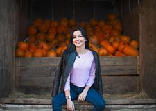 Fashionable beautiful young girl at the autumn pumpkin patch background. Having fun and posing. Toned in retro style royalty free stock image