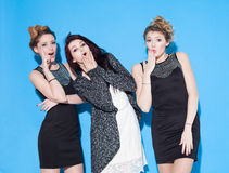 Fashionable beautiful young girlfriends standing together near a blue background. Two blondes and a brunette. Having funny and pos Stock Images
