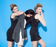 Fashionable beautiful young girlfriends standing together near a blue background. Two blondes and a brunette. Having funny and pos Stock Image