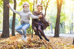 Fashionable beautiful young girlfriends walking together in the autumn park background. Having fun and posing royalty free stock photography