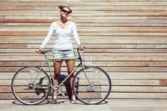 Fashionable beautiful young Pretty girl in shorts and t-shirt stands with bicycle fix gear nex to the wall of wooden planks bright Stock Photo