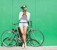Fashionable beautiful young Pretty girl in shorts and t-shirt and sunglasses stands with  bicycle fix gear nex to green wall brigh Stock Photo