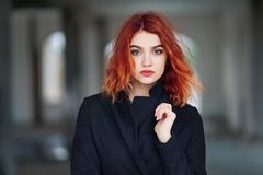 Fashionable beautiful young red-haired girl in a black coat posing in an abandoned room looking directly  into the camera. Fashionable beautiful young red-haired stock images