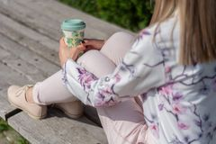 Fashionable girl with a cup of coffee on legs sitting on a bench in a park royalty free stock images