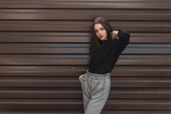 Fashionable beautiful young woman in an elegance black sweater in stylish black plaid pants posing on a spring day in the city. Near a metallic brown wall royalty free stock photography